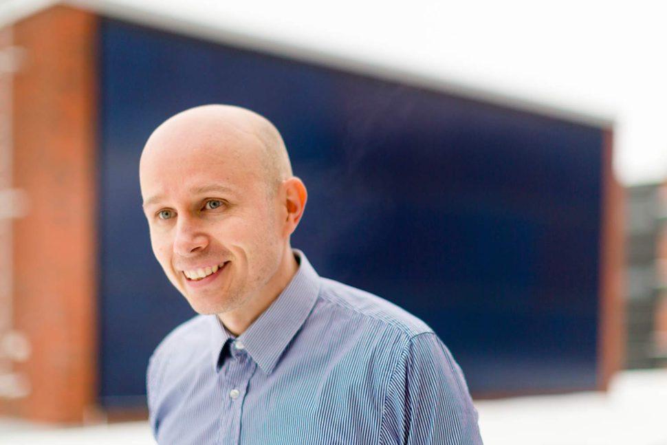 Energia-asiantuntija hymyilee sinisessä paidassa