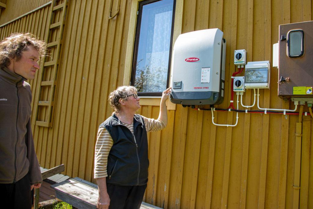 Tuomas ja Eija Naakka tutkivat talon seinustalla olevaa aurinkosähkömittaria