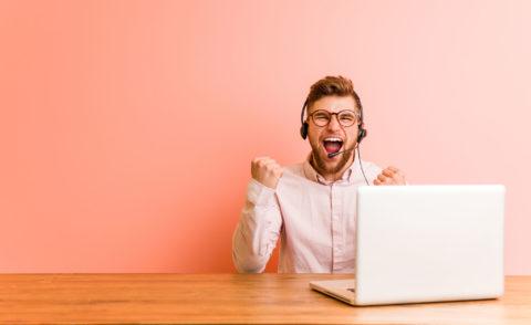 Mies iloitsee tietokoneen vieressä