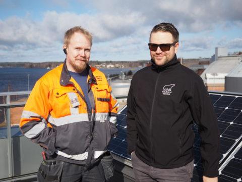 Kaksi miestä seisoo aurinkopaneelien edessä