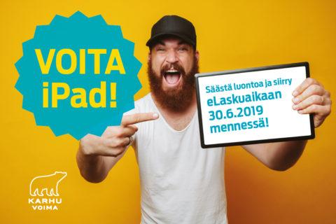 Kampanjakuva, jossa mies osoittaa iPadia, jossa on Karhu Voima -kilpailu
