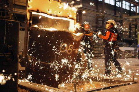 Mies työstää sulaa rautaa valimossa