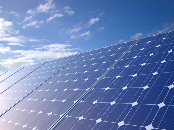Aurinkopaneelit kylpevät auringossa taivasta vasten